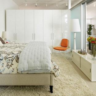 Diseño de dormitorio urbano con paredes blancas y suelo de madera clara