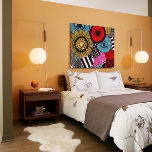 Идея дизайна: спальня в стиле лофт с оранжевыми стенами и паркетным полом среднего тона