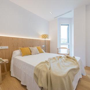 Imagen de dormitorio nórdico, de tamaño medio, sin chimenea, con paredes blancas y suelo de madera clara