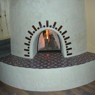 Ejemplo de dormitorio principal, de estilo americano, grande, con paredes beige, suelo de madera clara, chimenea de esquina y marco de chimenea de yeso