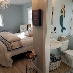 Example of a mid-sized classic master laminate floor and brown floor bedroom design in Other with gray walls and no fireplace