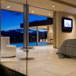 Идея дизайна: большая хозяйская спальня в стиле модернизм с бежевыми стенами и полом из травертина без камина