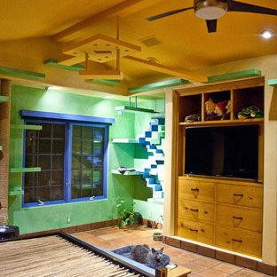Immagine di una camera degli ospiti bohémian con pareti verdi e pavimento in terracotta