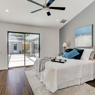 Ejemplo de dormitorio principal, retro, sin chimenea, con paredes blancas, suelo de bambú y suelo marrón