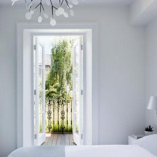 Modelo de dormitorio principal, actual, pequeño, con paredes blancas y suelo de madera oscura