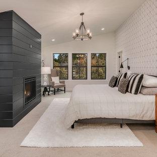Ejemplo de dormitorio principal, de estilo de casa de campo, grande, con paredes blancas, moqueta, chimenea tradicional, marco de chimenea de madera y suelo gris
