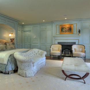 Modelo de dormitorio clásico con paredes azules, chimenea tradicional y marco de chimenea de piedra