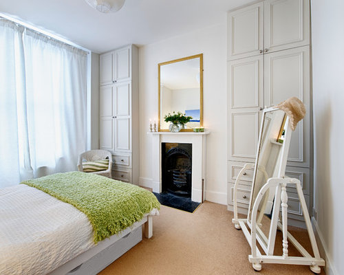 Mid sized traditional guest carpeted bedroom idea in London with white  walls  a standard. Our 25 Best Bedroom with a Wood Fireplace Surround and White Walls