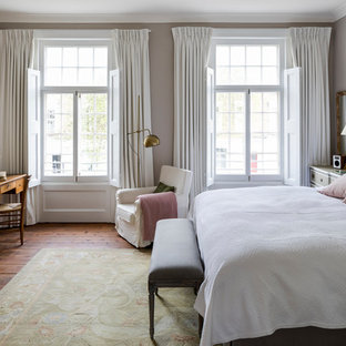 Traditional master bedroom in London with grey walls, a stone fireplace surround, medium hardwood flooring, a standard fireplace and brown floors.