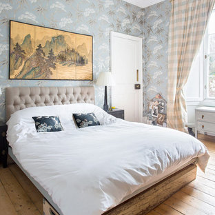 This is an example of a medium sized eclectic master bedroom in Edinburgh with multi-coloured walls, medium hardwood flooring and brown floors.