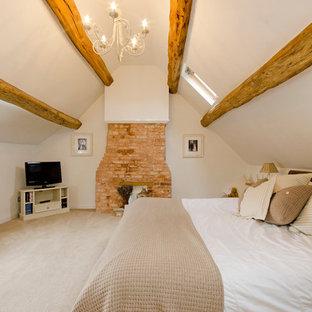 Foto di una camera da letto country con pareti bianche, moquette, camino classico e cornice del camino in mattoni