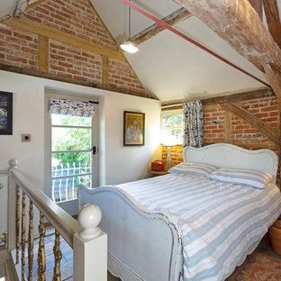 Modelo de dormitorio tipo loft, de estilo de casa de campo, con paredes rojas