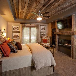 Пример оригинального дизайна: хозяйская спальня среднего размера в стиле рустика с бежевыми стенами, ковровым покрытием, горизонтальным камином, фасадом камина из дерева и бежевым полом