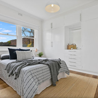Photo of a contemporary master bedroom in Hobart with white walls, medium hardwood floors and brown floor.