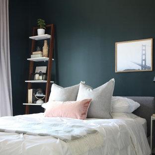 Modelo de dormitorio principal, ecléctico, pequeño, con paredes verdes, suelo laminado y suelo marrón