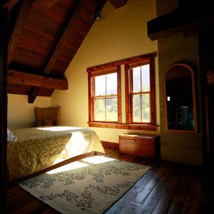 Ejemplo de dormitorio tipo loft, rural, grande, con paredes amarillas, suelo de madera en tonos medios, chimenea tradicional, marco de chimenea de hormigón y suelo marrón