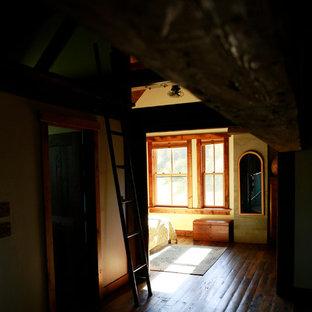 Idéer för ett stort rustikt sovloft, med gula väggar, mellanmörkt trägolv, en standard öppen spis och en spiselkrans i betong