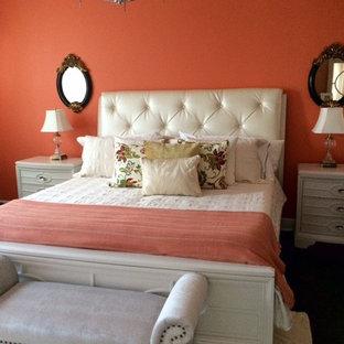 Ispirazione per una camera degli ospiti minimal di medie dimensioni con pareti arancioni, moquette e nessun camino