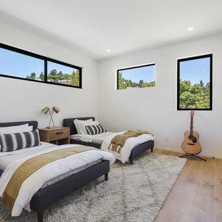 Modernes Gästezimmer mit weißer Wandfarbe, braunem Holzboden und braunem Boden in Sacramento