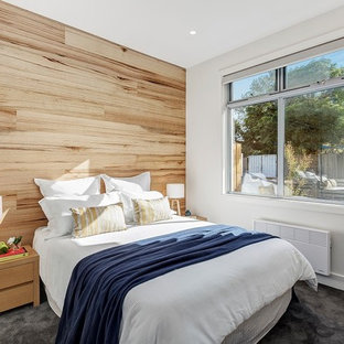 Transitional bedroom in Melbourne with white walls, carpet and grey floor.