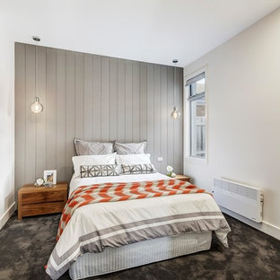 Scandinavian master bedroom in Melbourne with white walls, carpet and grey floor.