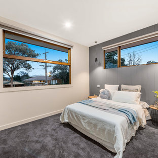 This is an example of a scandinavian master bedroom in Melbourne with beige walls, carpet and grey floor.