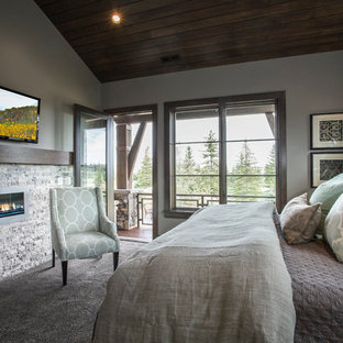 Example of a mountain style guest carpeted bedroom design in Salt Lake City with gray walls, a ribbon fireplace and a stone fireplace