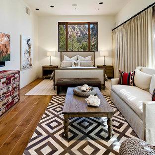 フェニックスのサンタフェスタイルのおしゃれな寝室 (白い壁、無垢フローリング、茶色い床)