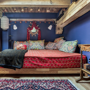 Example of a mid-sized mountain style loft-style light wood floor and brown floor bedroom design in Chicago with blue walls and no fireplace