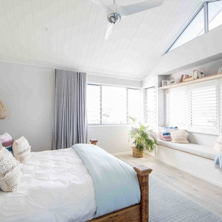 Design ideas for a mid-sized beach style loft-style bedroom in Gold Coast - Tweed with white walls, painted wood floors and grey floor.