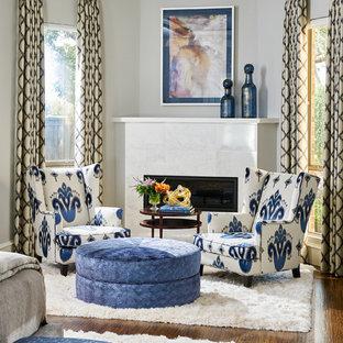 Diseño de dormitorio principal, tradicional, con paredes grises, suelo de madera en tonos medios, marco de chimenea de piedra y chimenea de esquina