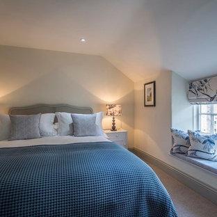 Foto de dormitorio principal, campestre, grande, con paredes beige, moqueta, chimenea tradicional, marco de chimenea de metal y suelo beige
