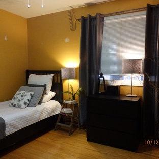 Diseño de habitación de invitados ecléctica, pequeña, sin chimenea, con paredes amarillas y suelo de madera clara