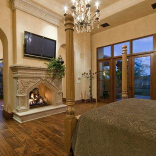 Foto på ett mycket stort medelhavsstil sovrum, med beige väggar, travertin golv, en standard öppen spis och en spiselkrans i sten