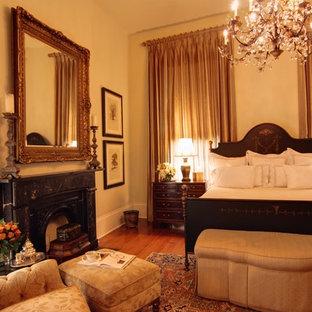 На фото: большая гостевая спальня в классическом стиле с бежевыми стенами, темным паркетным полом, стандартным камином и фасадом камина из штукатурки с