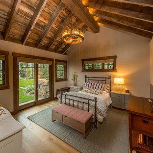 Foto de habitación de invitados rural, de tamaño medio, sin chimenea, con paredes beige, suelo de madera clara y suelo beige