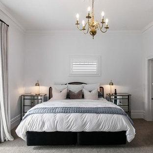 オークランドの大きいヴィクトリアン調のおしゃれな主寝室 (白い壁、カーペット敷き、標準型暖炉、木材の暖炉まわり、グレーの床)
