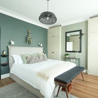 Exemple d'une chambre parentale tendance de taille moyenne avec un mur vert, un sol en bois clair et un sol beige.