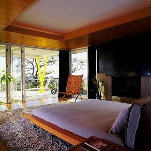 Inspiration för sovloft, med en spiselkrans i betong, grå väggar, mellanmörkt trägolv och en standard öppen spis