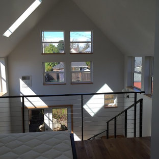This is an example of a small modern loft-style bedroom in Portland with white walls and medium hardwood floors.