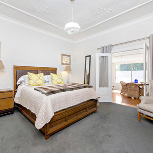 This is an example of a country guest bedroom in Other with white walls, carpet and grey floor.