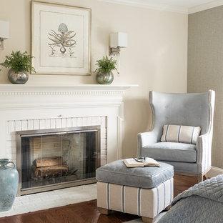 Diseño de dormitorio principal, tradicional, con paredes beige, chimenea tradicional, marco de chimenea de ladrillo y suelo de madera oscura