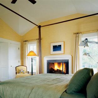 Foto di una camera da letto country con pareti gialle e camino classico