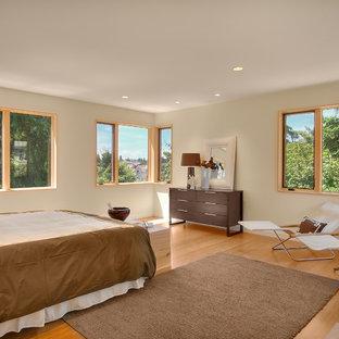 Imagen de dormitorio principal, minimalista, de tamaño medio, con paredes beige y suelo de bambú