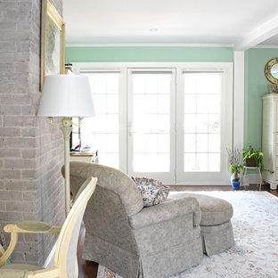 Modelo de habitación de invitados tradicional, grande, sin chimenea, con paredes verdes, suelo de madera oscura, marco de chimenea de ladrillo y suelo marrón