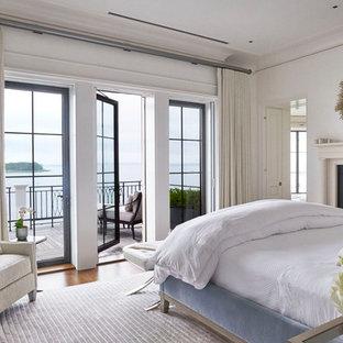 バンクーバーのトラディショナルスタイルのおしゃれな寝室 (白い壁、無垢フローリング、標準型暖炉、茶色い床) のレイアウト