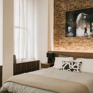 Urban master medium tone wood floor bedroom photo in New York with no fireplace and beige walls