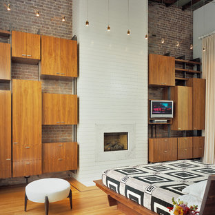 Example of a trendy bedroom design in New York with a standard fireplace and a brick fireplace