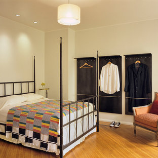 Eclectic medium tone wood floor bedroom photo in New York with beige walls