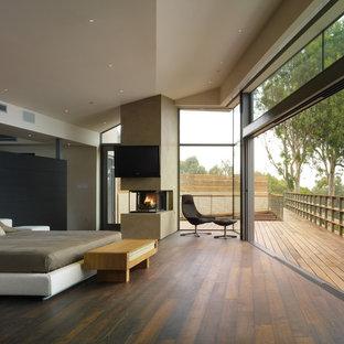 Ejemplo de dormitorio principal, actual, de tamaño medio, con suelo de madera oscura, chimenea de doble cara, paredes blancas y marco de chimenea de yeso